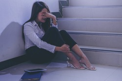 Depressed businesswoman sitting at the office stairway. Hopeless, sadness, depression, crying,  and disappointed.