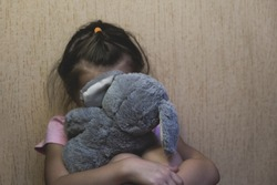 Depressed child sitting and hidden behind her toy teddy bear. domestic and violence, beaten sitting at the wall, Domestic violence. Copy space.