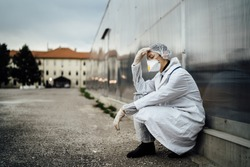 Depressed crying doctor with mask having mental breakdown.Fear,anxiety,panic attack due to coronavirus outbreak.Psychological effects of COVID-19.PTSD.Mental health,coping with death