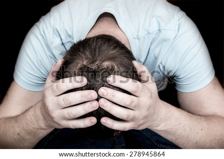 Depressed crying scared man holding his head in his hands sitting on floor over black background. Despair, depression, hopelessness, addiction concept.