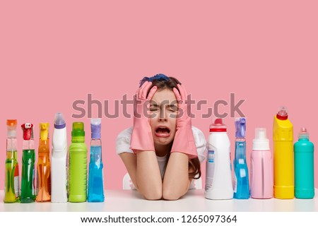 Depressed crying woman looks stressfully, keeps both hands on head, wears protective gloves, surrounded with many cleaning products, feels fatigue of busy day and cleaning house. Female janitor indoor