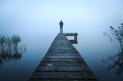 Depressed emotions concept: man standing at the end of a jetty, on a foggy, autumn morning.
