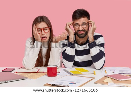 Depressed female and male groupmates have unhappy looks, express negative feelings, sit at workplace together, sad to have deadline for preparing project work, isolated over pink background.