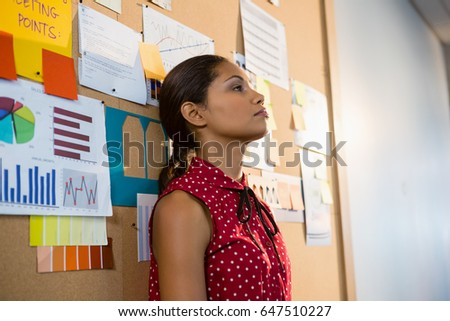 Depressed female executive leaning on bulletin board in office Foto stock ©