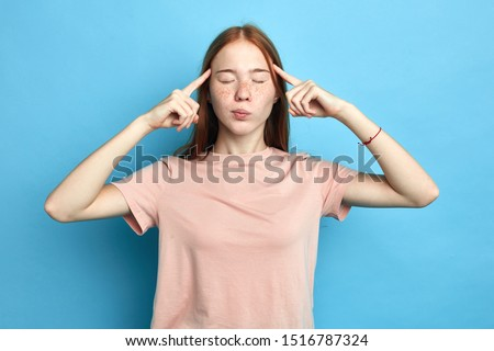depressed frustrated upset serious girl concentrated on thinking, trying to remember something, woman has terrible headache, girl massaging her temples. close up portrait. isolated blue background