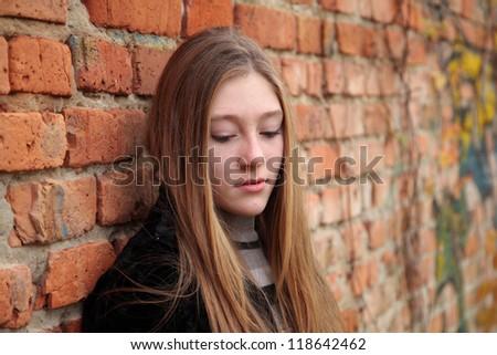 Depressed girl near the wall - stock photo