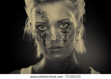 Depressed girl with dirt on her face, closeup. Studio shot, sepia