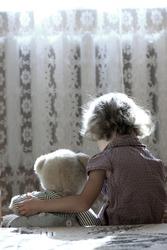 Depressed little girl hugging teddy bear