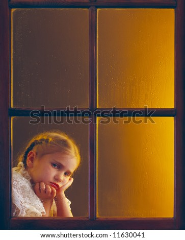 Depressed, lonely and abused little girl behind a rain-splattered window