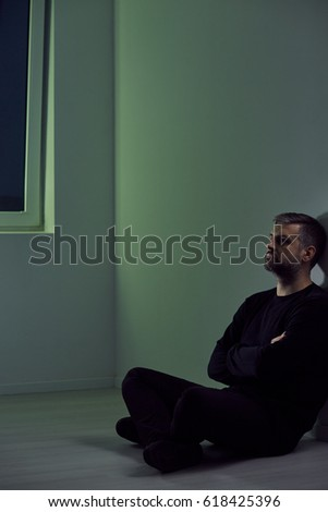 Depressed Lonely Man Sitting On A Floor In An Empty Room At Night 618425396