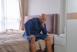 Depressed lonely old elderly black man. African American people sitting on bed with windows in bedroom at home in early morning. Quarantine lifestyle. Unhappy life.