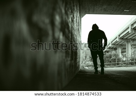 Depressed looking silhouette of a man walking in tunnel stock photo