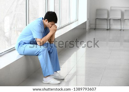 Depressed male medical assistant sitting on window sill in clinic