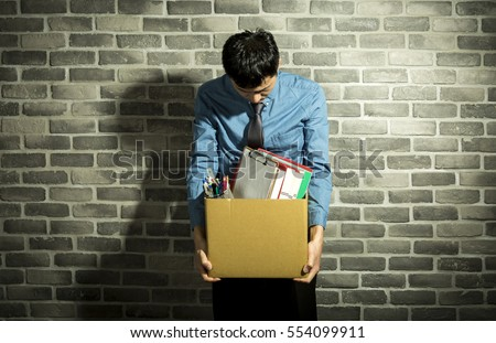 depressed man holding box in his hands, with office supplies inside, wall background - Shutterstock ID 554099911