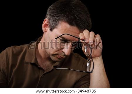 Depressed man holding glasses on black background #34948735