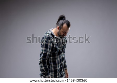 Depressed man in casual plaid shirt with ponytail standing with a hang dog expression and bowed head looking down at the floor isolated on grey with copy space