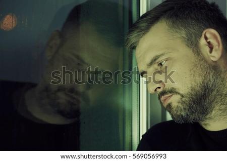 Depressed man looking sadly through the window