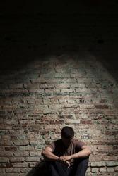 Depressed man sitting alone against brick wall.