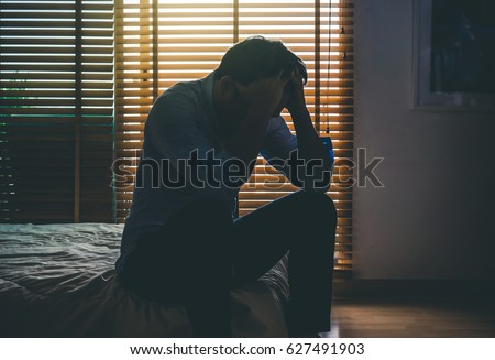 depressed man sitting head in hands on the bed in the dark bedroom with low light environment, dramatic concept