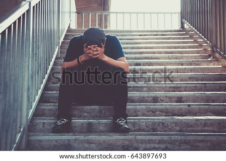 Depressed man sitting head in hands on the footbridge, Sad man, Cry, drama concept