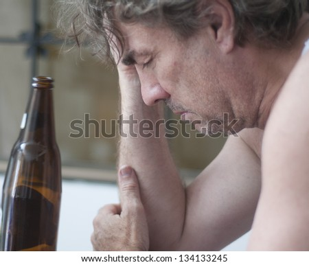 Depressed man with alcohol bottle