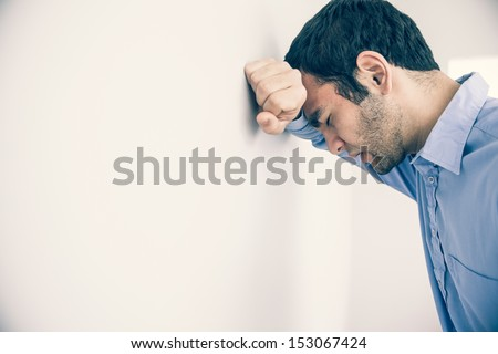 Depressed man with fist clenched leaning his head against a wall Foto d'archivio ©
