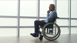 Depressed Middle-aged Lonely Man, Frustrated Mature Man, Sitting Alone in a Wheelchair By the Window. Solitude, Care, Retirement, Injury, Disability. Rehab Client, Hard Recovery.