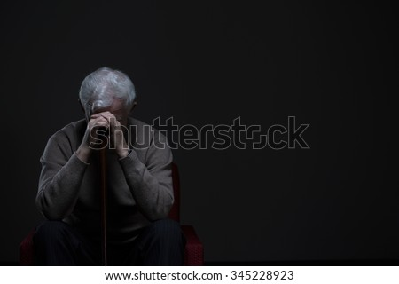 Depressed old man hiding his face behind hands