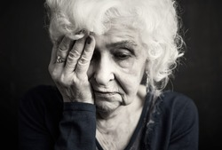 Depressed old woman covering her face