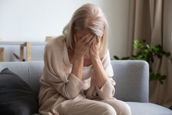 Depressed older woman covering face with hands, crying, feeling desperate. Unhappy mature grandmother experiencing grief, relative's death, bad news. Stressed elder lady suffering from loneliness.
