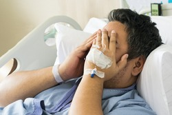 depressed patient asian man 40 on hospital bed with hand cover on his face, worry or mental health concept with copy space