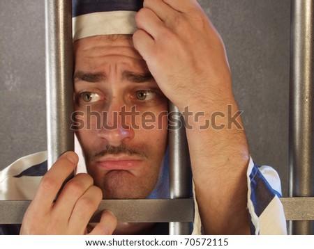 Depressed prisoner in a prison cell.
