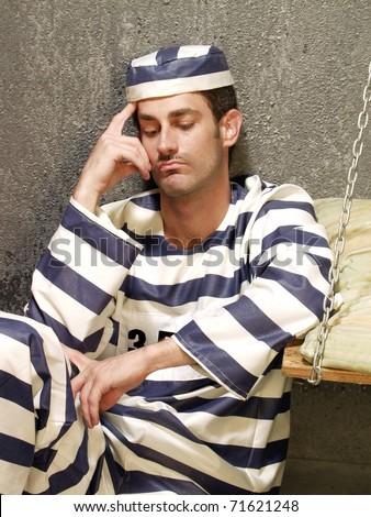 Depressed prisoner in a prison cell. Boring prisoner. - stock photo
