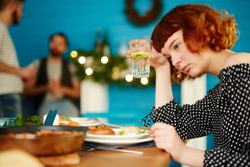Depressed red-haired woman sitting alone at table, drinking cocktail and thinking while her friends having fun in background