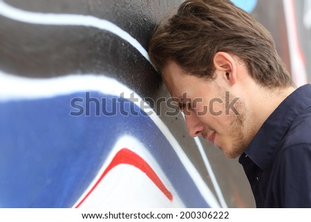 Depressed sad teenager boy lamenting with his head against a wall outdoors