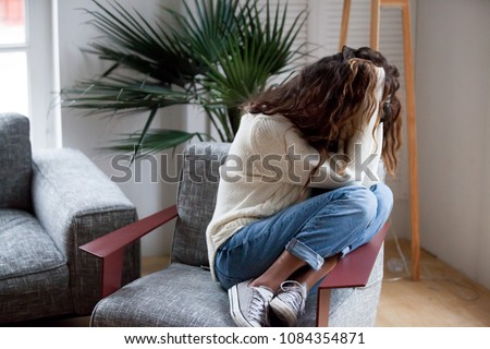 Depressed sad woman holding head in hands sitting on armchair at home, harassment abuse teenage victim feeling bad, heartbroken upset girl crying having mental problem or dangerous drug addiction