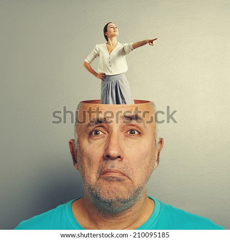 depressed senior man with open head. young smiley woman standing in the head and pointing at something. photo over grey background
