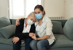 Depressed senior mother and daughter wearing medical mask crying and embracing each other grieving loss of loved ones fighting the Coronavirus. People and families affected by COVID-19 outbreak.