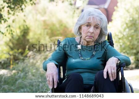 Depressed Senior Woman In Wheelchair Sitting Outdoors Stock photo ©