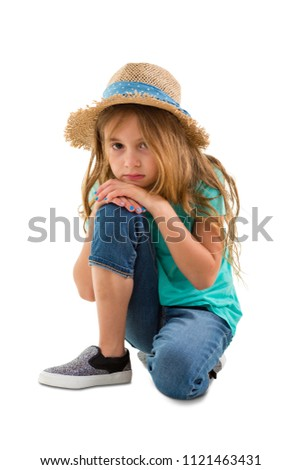 Depressed solemn little girl staring at the camera as she kneels resting her chin on her knee isolated on white