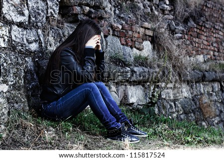Depressed teenage girl with hands over her face,