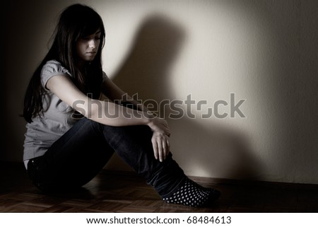 Depressed teenager girl sitting on floor.
