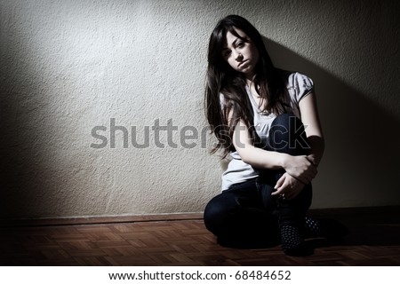 Depressed teenager girl sitting on floor.