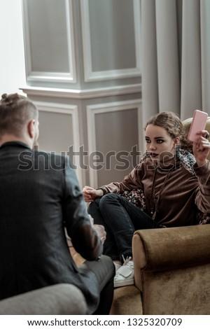 Depressed teenager. Professional counselor wearing dark jacket listening to depressed teenager