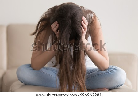 Depressed teenager sitting holding head in hands, stressed sad young woman having mental problems, feeling bad, need psychological help, addicted heartbroken girl experiencing adolescence crisis