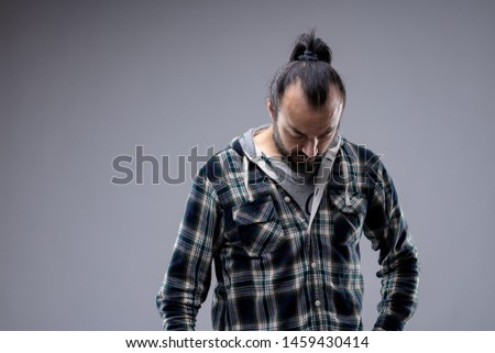 Depressed unmotivated man staring down at the floor with a dejected look and demeanour isolated on grey with copy space