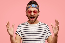 Depressed unshaven fashionable young hippie male shouts loudly and gestures with hands, expresses aggressive feeling to someone, wears trendy sunglasses and headband, isolated over pink background