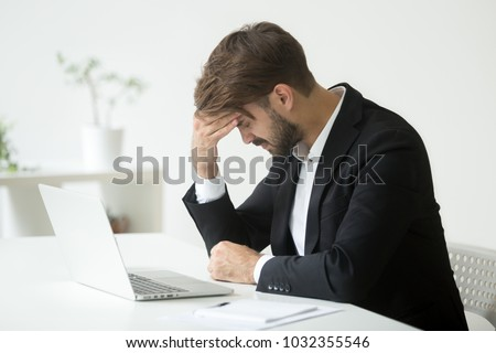 Depressed unsuccessful businessman feels terrible headache, distraught stressed entrepreneur regrets of business mistake shocked by bankruptcy desperate after failure sitting at work desk with laptop