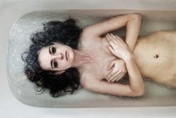 Depressed woman lies in bath