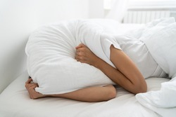 Depressed woman lying alone on bed covering head with pillow feeling afraid or depressed suffer from insomnia, loud sounds of neighbors, has mental problems after divorcing her husband. Loneliness.